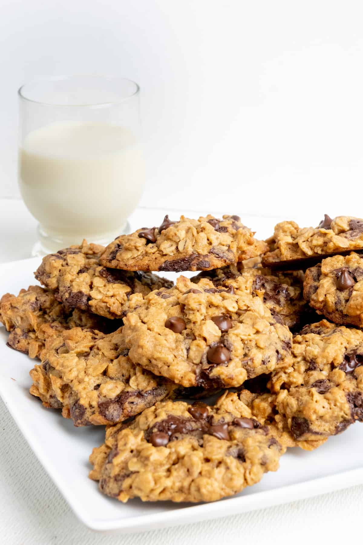 A pile of cookies on a plate, and in the background a glass of oat milk.