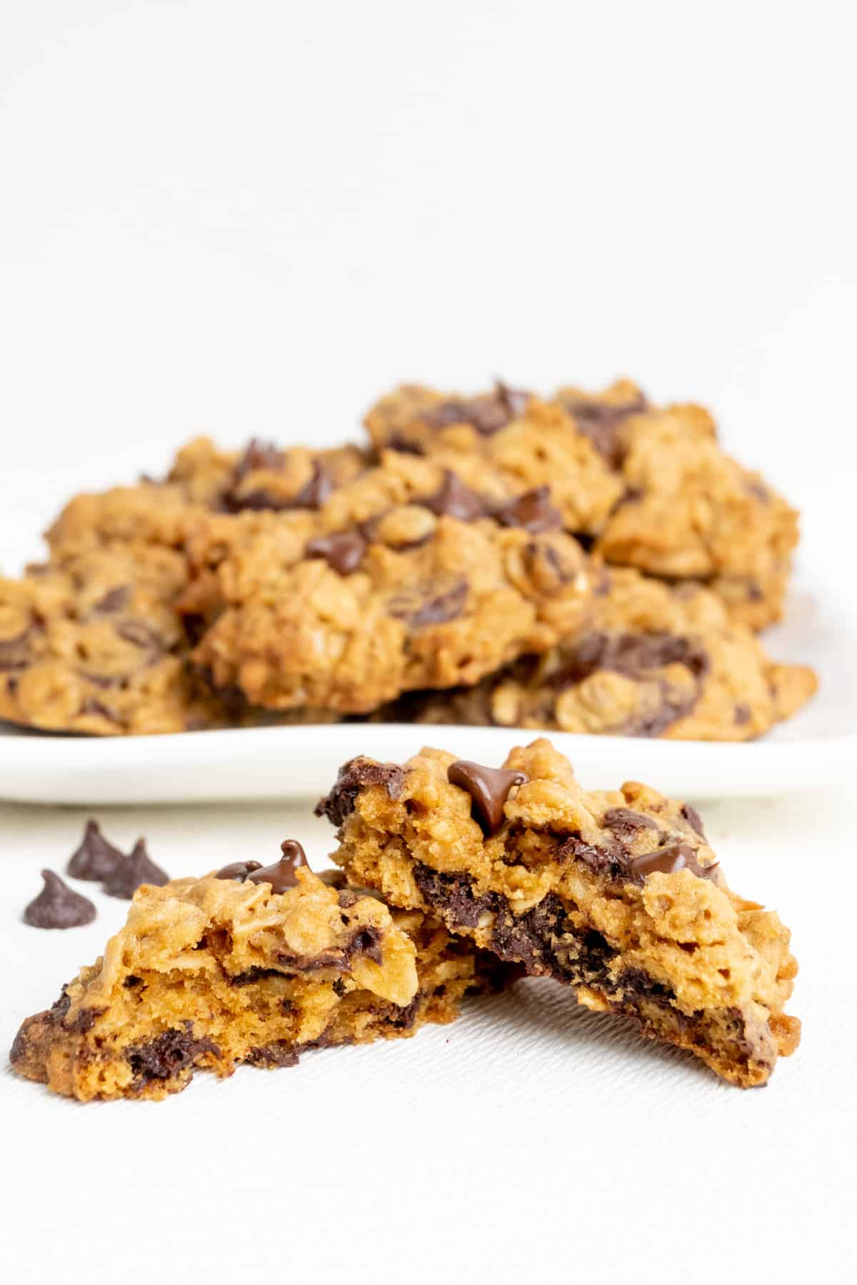 A cookie snapped in two revealing the flaky texture and chunks of chocolate inside.