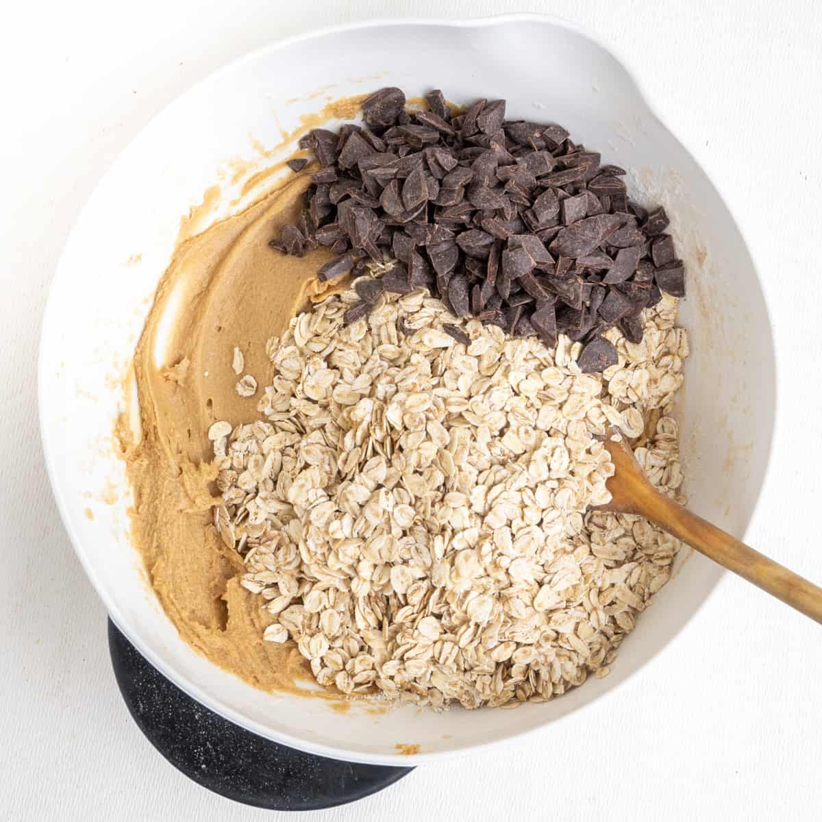 Rolled oats and chocolate chips are stirred into cookie dough.