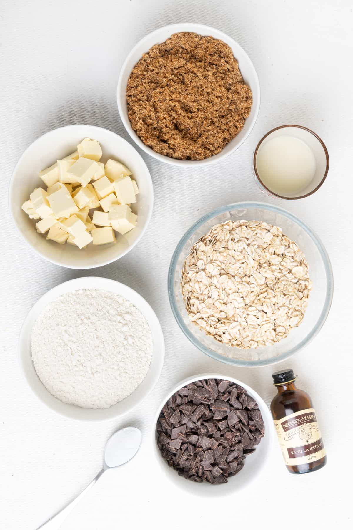 The ingredients for this recipe: Rolled oats, plain flour, soft brown sugar, cubes of vegan butter, oat milk, chocolate chips, baking powder and vanilla extract.