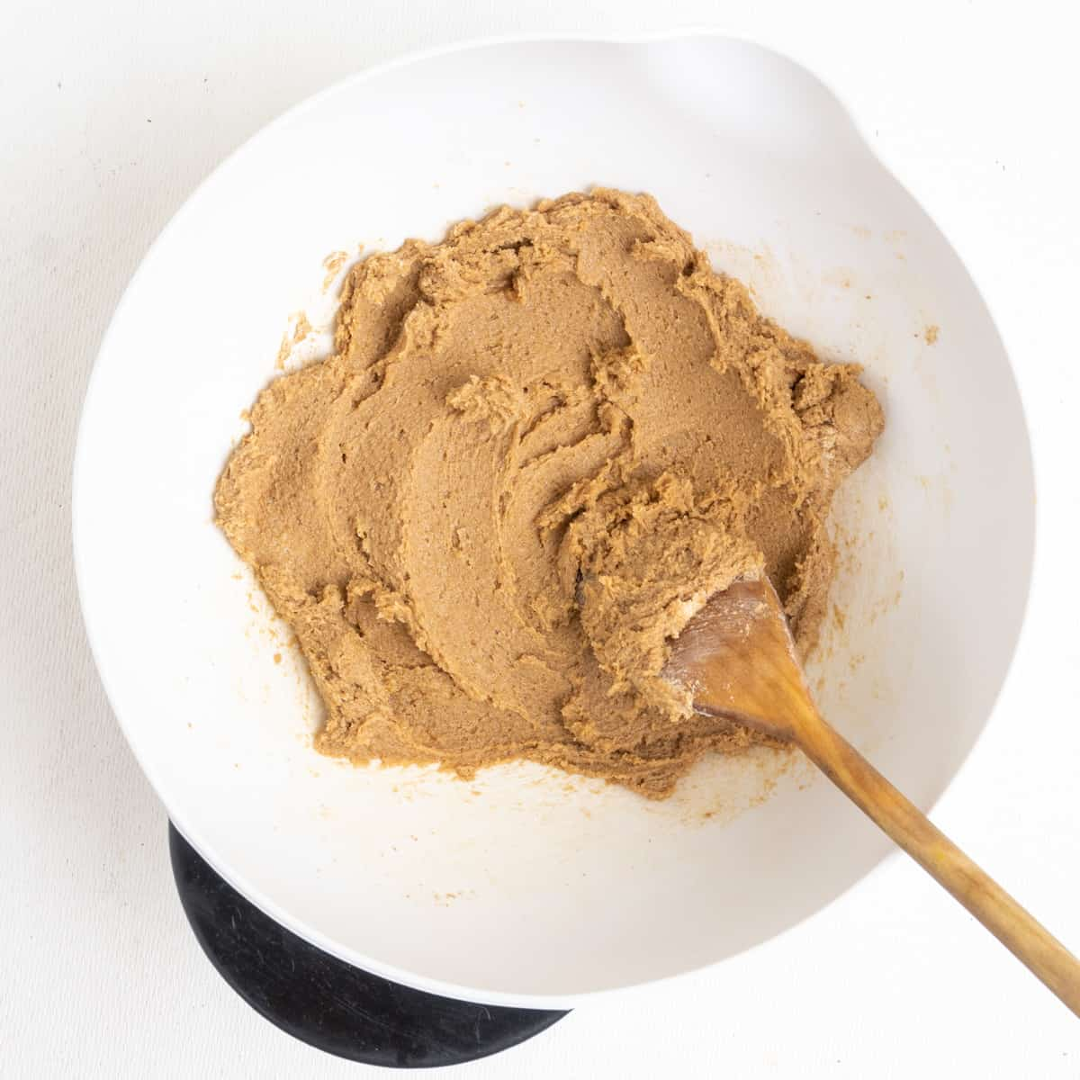Brown sugar and vegan butter creamed together in a mixing bowl using a wooden spoon.