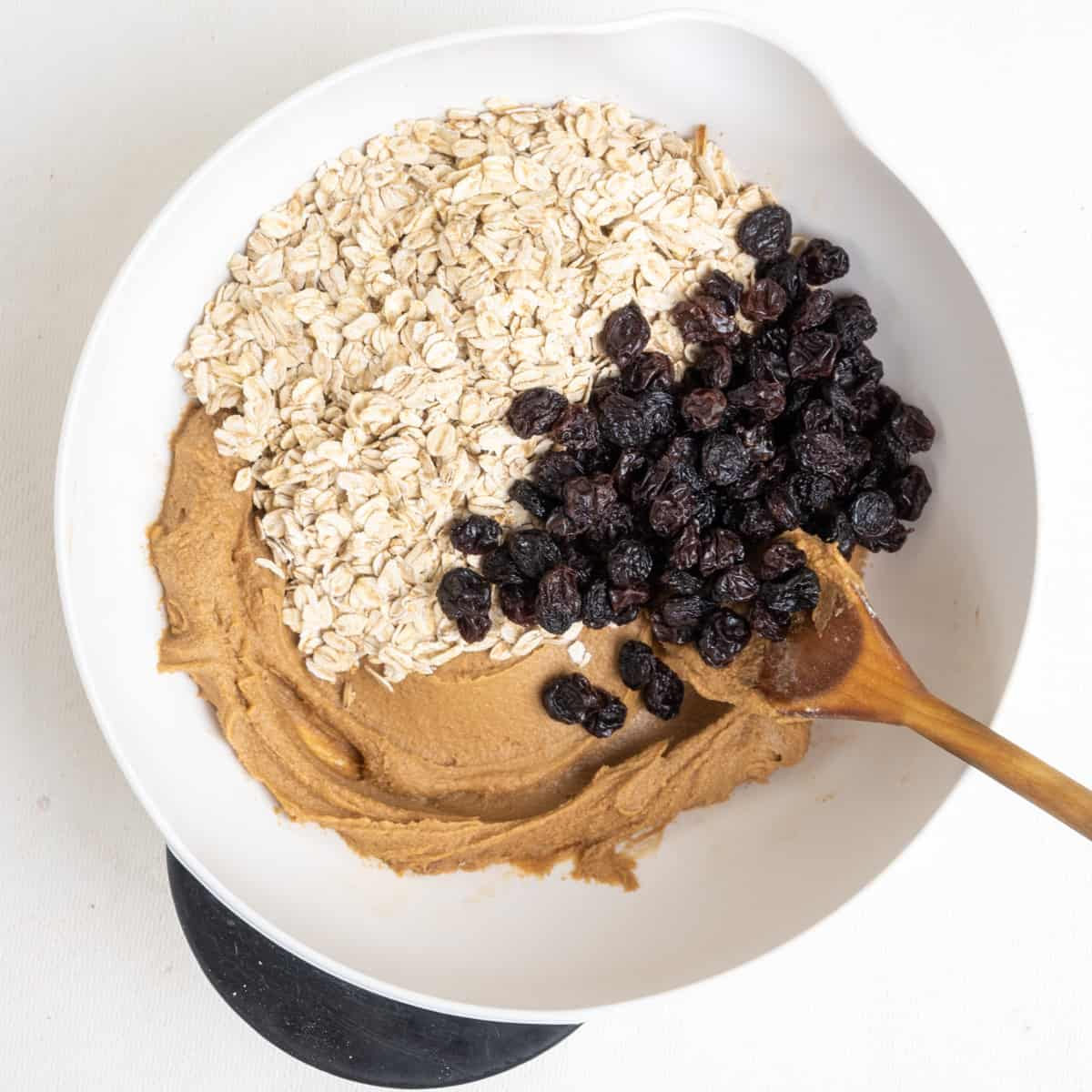 Oats and raisins with cookie dough in a mixing bowl.
