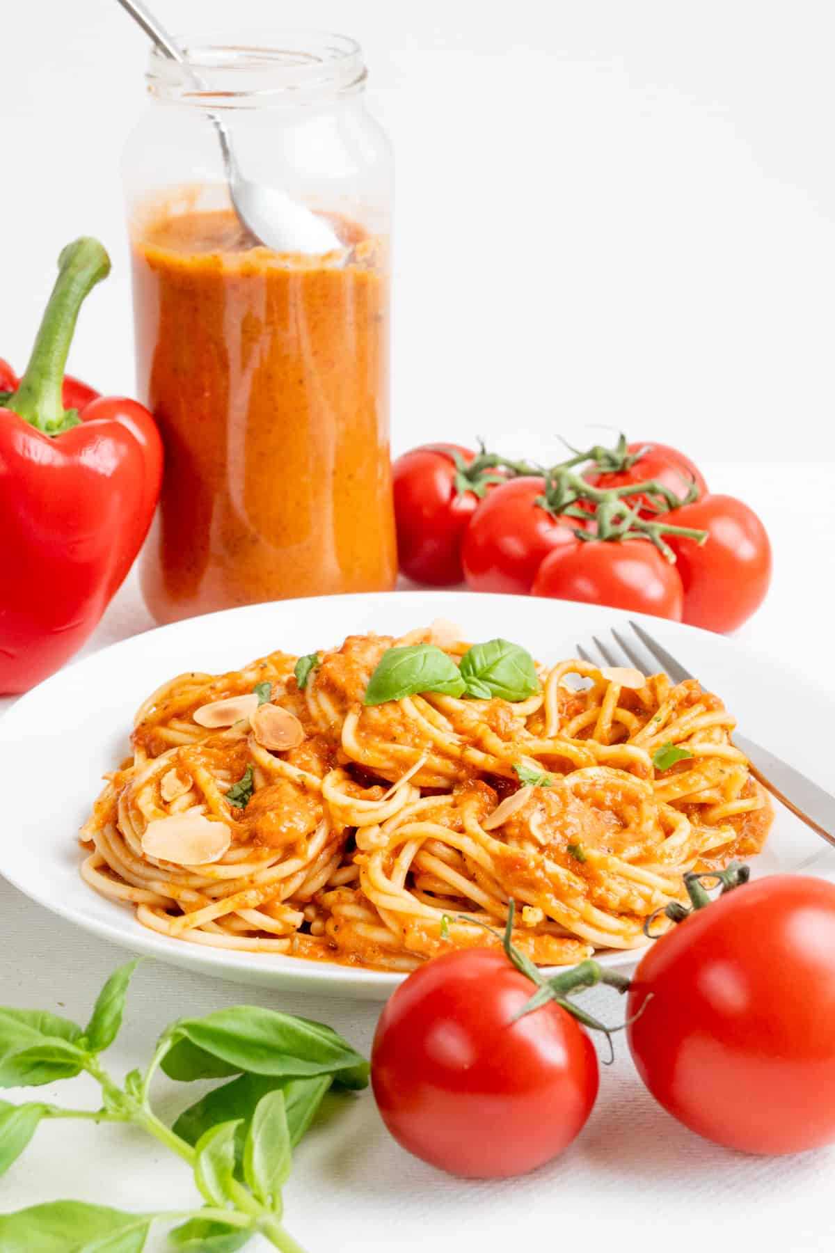 In the foreground fresh red vegetables next to a plate of red pepper and tomato pasta. In the background, a tall jar of dark orange sauce.