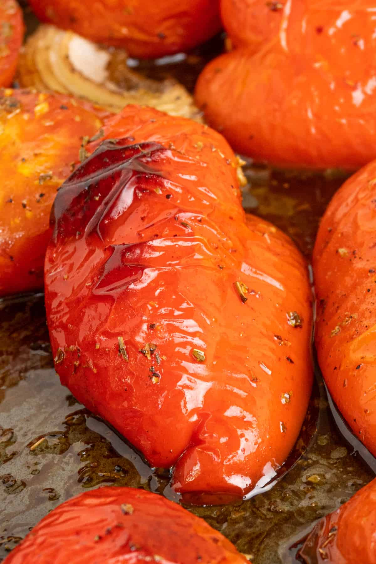 A roasted pepper. Its skin is coated in oil and herbs, slightly wrinkled and darkened in one place from the roasting.