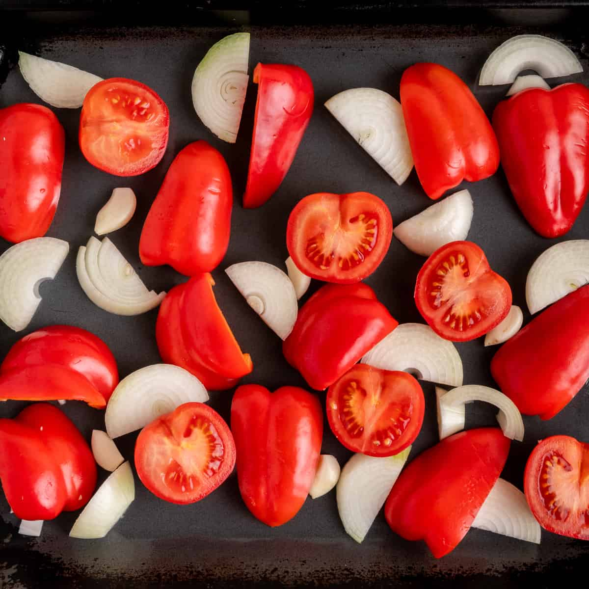 Large chunks of red peppers, tomatoes and onions and some whole garlic cloves on a roasting tray.