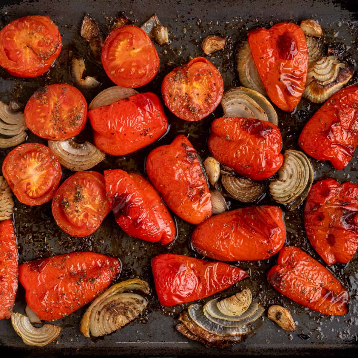 The peppers, tomatoes and onions after roasting, slightly wrinkled and browned in patches.
