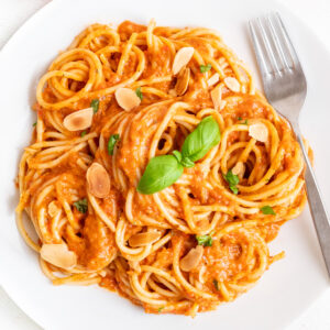 A plate of pasta in a red pepper and tomato sauce with a fork.