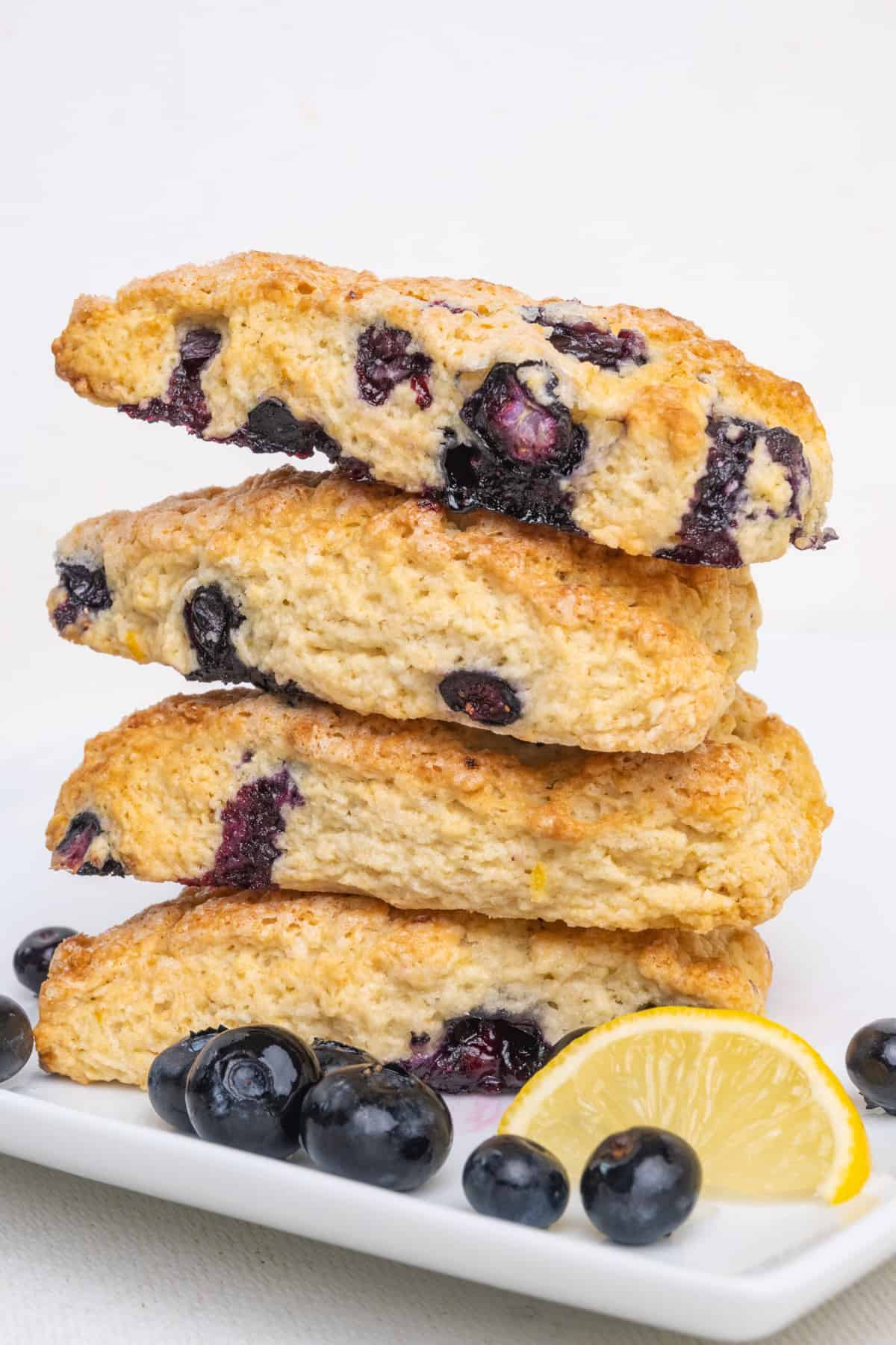 A stack of four vegan blueberry scones on a white plate.