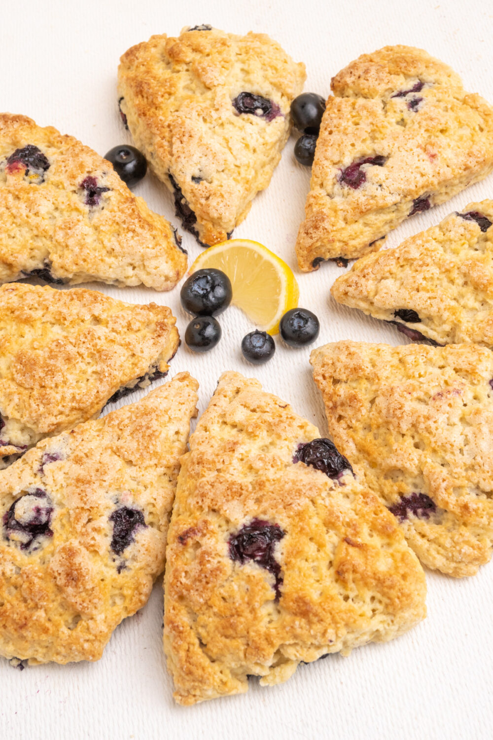 Wedge shaped blueberry scones arranged in a circle.