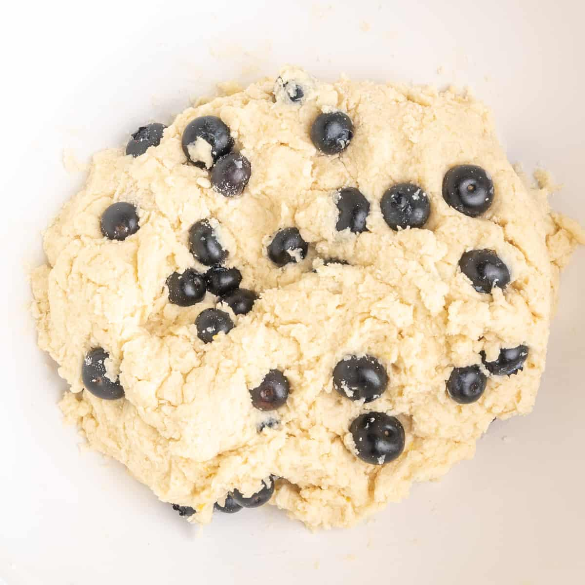 Incorporating the blueberries into the roughly mixed dough.