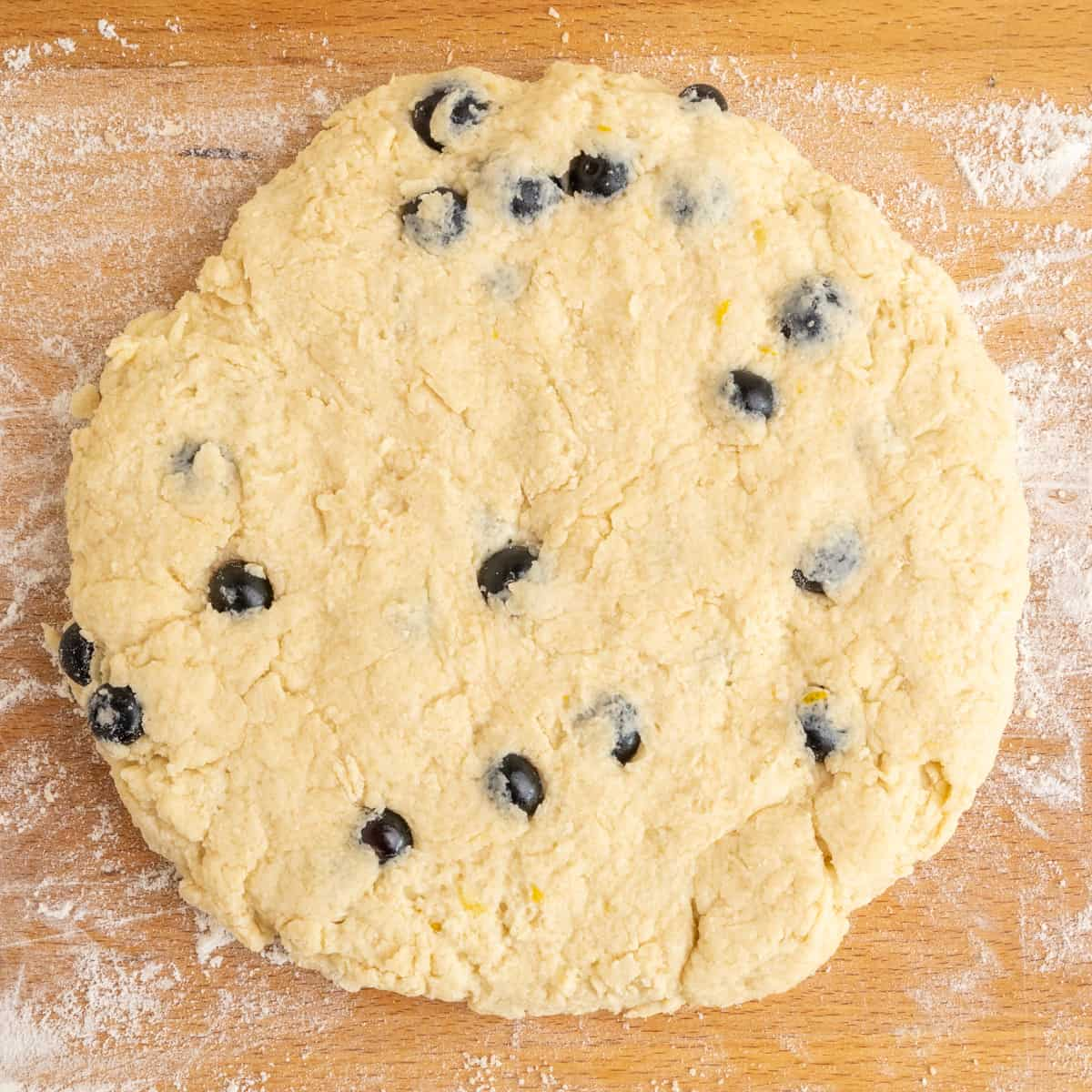 The blueberry scone dough formed into a disc on a lightly floured wooden board.