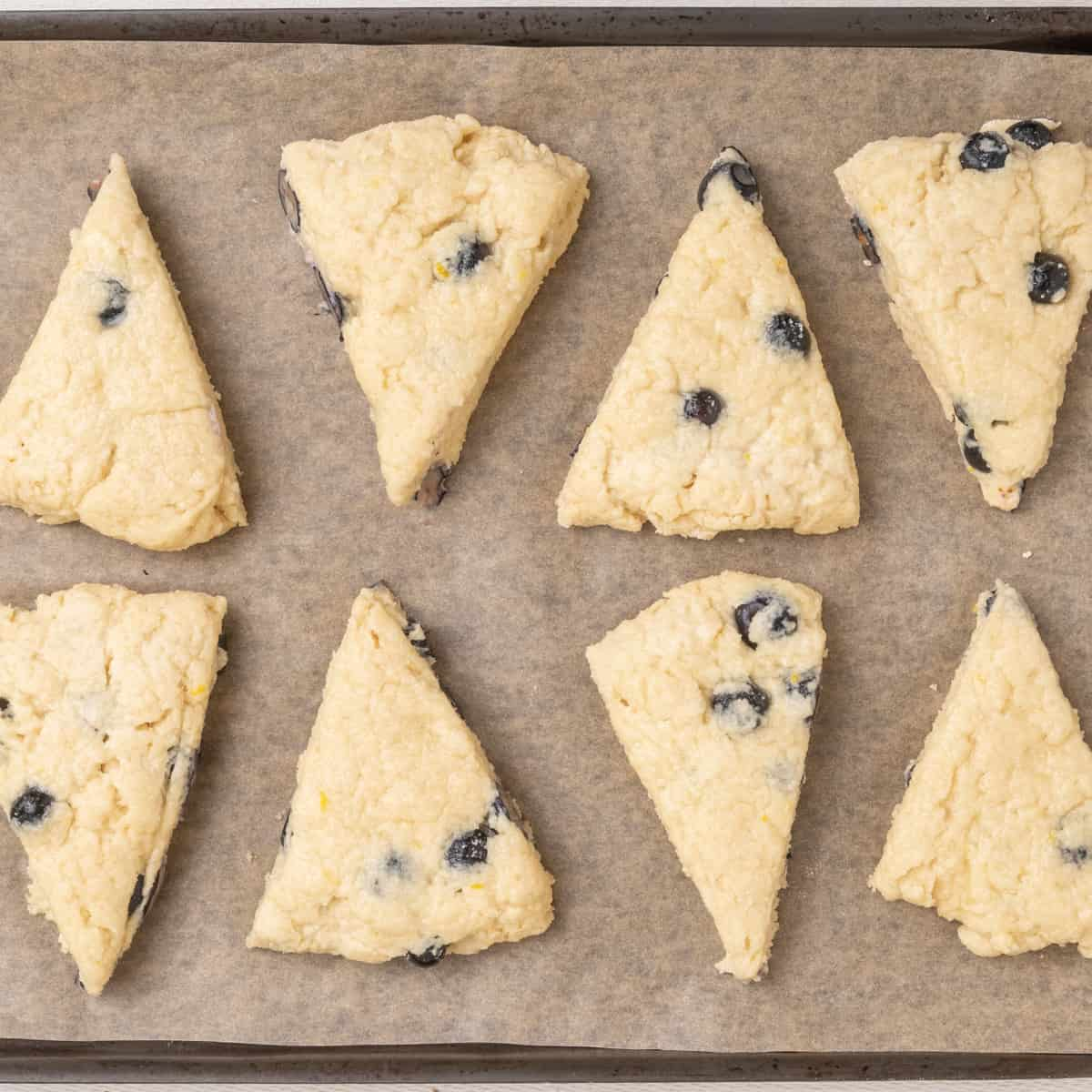Wedges of blueberry scone dough arranged on a line baking sheet.