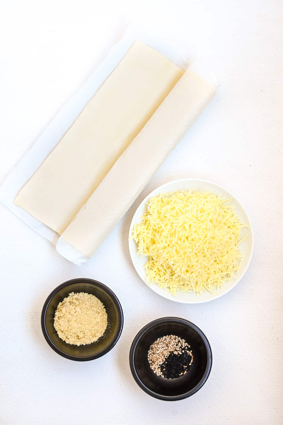 The main ingredients to make vegan cheese straws: Puff pastry, vegan cheese, sesame and nigella seeds and nutritional yeast flakes.