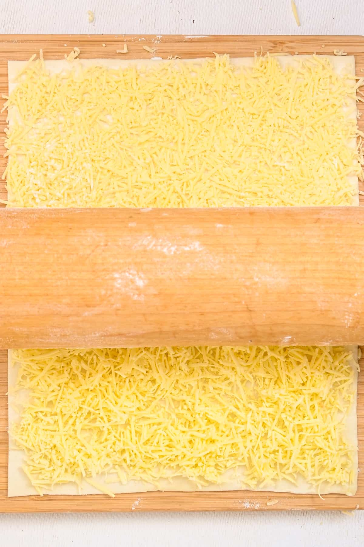 Grated cheese is firmed down on pastry with a rolling pin.