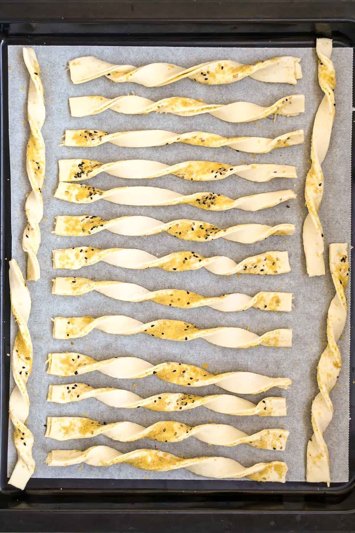 The straws are twisted into spirals and set down on a lined baking tray ready for baking.
