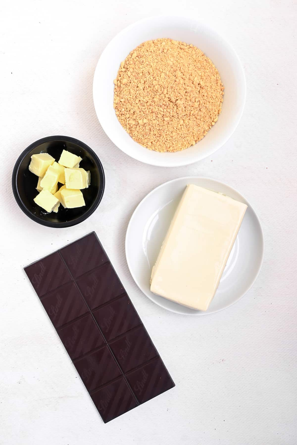 A bar of dark chocolate, vegan butter, a block of silken tofu and crumbled biscuits.