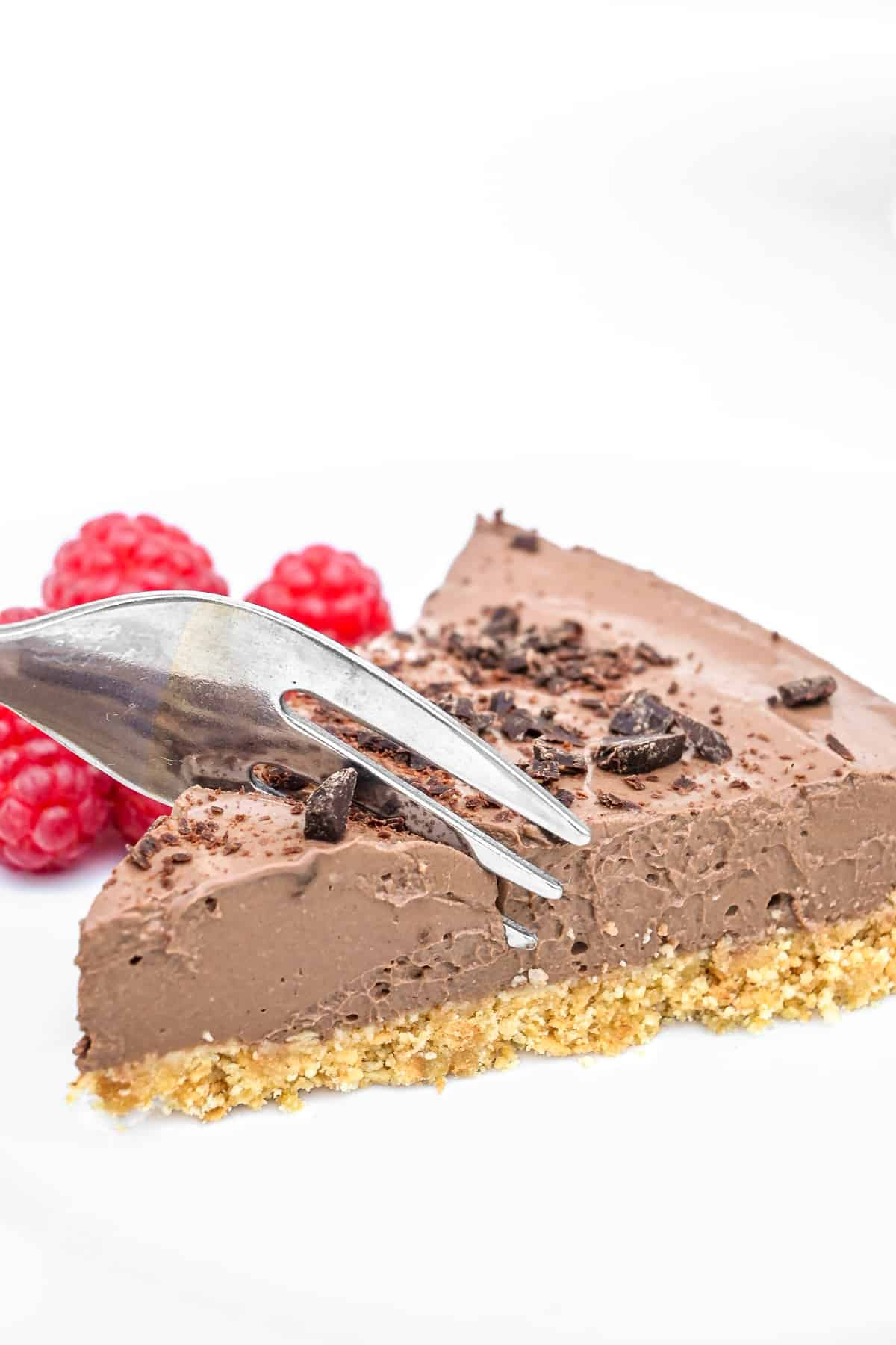 A cake fork digging into the smooth, soft but firm, chocolate filling of a slice of tart.